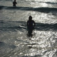 Lady at evening bath on Cala Tarida beach